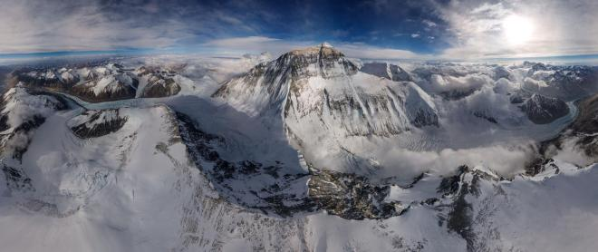 This photograph is no casual snapshot. It shows a breathtaking 360-degree view of a tall, pointy mountain in the middle of a snowy mountain range.