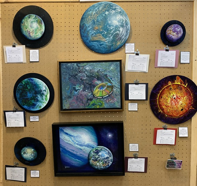 This photo shows an art show display panel from the SpikeCon Art Show, filled with eight examples of Lucy A. Synk's space art.