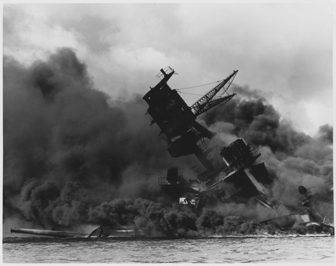 This is a classic photo of the USS Arizona being sunk at Pearl Harbor in 1941. The photographer is unknown.