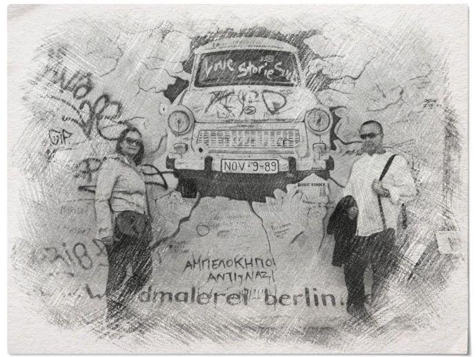 Instantánea en blanco y negro ante un grafiti del Muro de Berlín