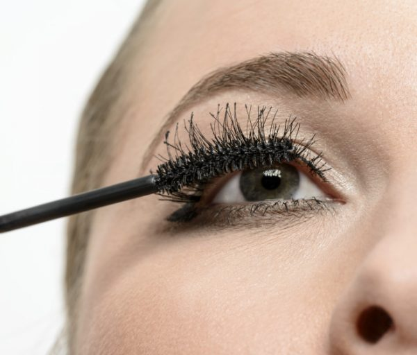 woman with green eye applying mascara.low angle view.