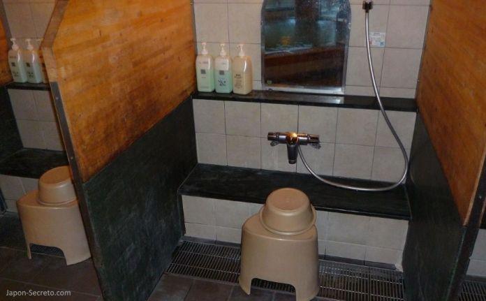 Baños tradicionales en Japón: zona de baño y aseo de un onsen. Cubo, taburete y jabones.