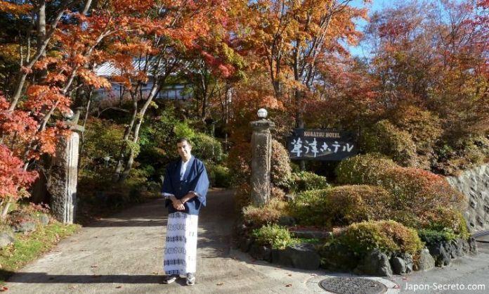 En la puerta del Kusatsu Hotel vestido con yukata durante el momiji (otoño)