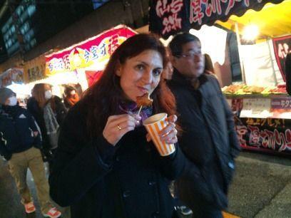 """Comiendo pollo frito (karaage) en uno de los puestos callejeros de comida o """"yatai"""". Festival Tōka Ebisu Taisai (十日えびす大祭) o """"Gran Festival del décimo día de Ebisu"""" en enero en el santuario Imamiya Ebisu de Ōsaka (今宮戎神社)"""