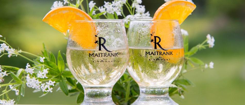Deux verres de Maitrank avec tranches d'orange et fleurs de gaillet odorant en arrière plan