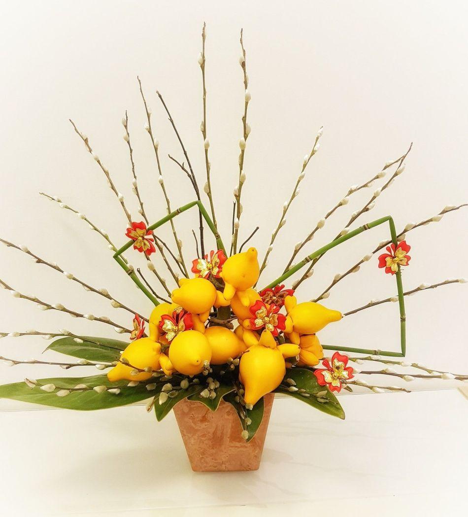 Arrangement floral à base de morelle mammiforme avec branches de chatons de saule.