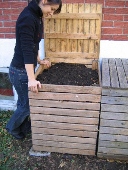 Fille qui regarde un composteur plein de compost.