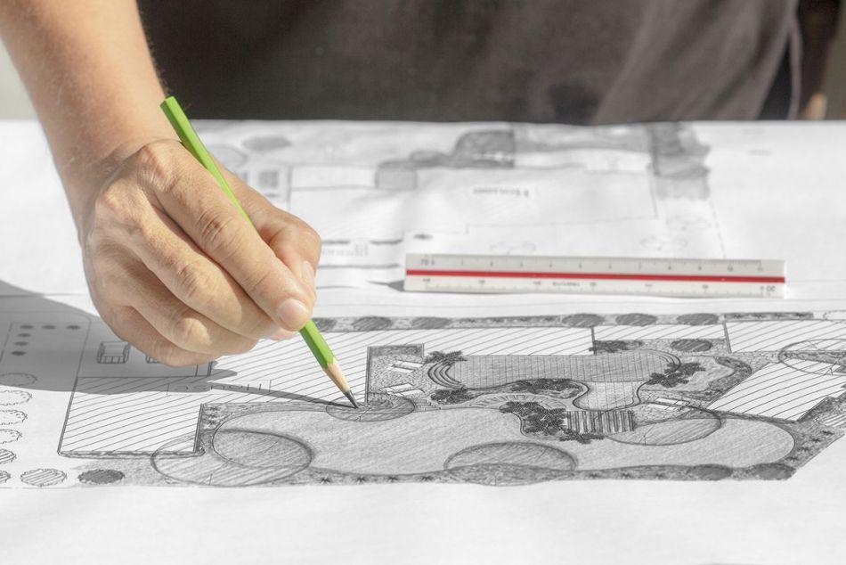 Main qui dessine un plan d'aménagement.