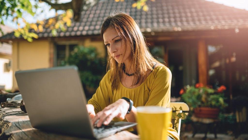 Femme travaillant sur un ordinateur sur une table sur la terrasse.