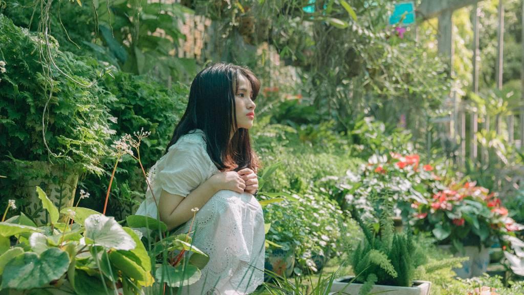 Femme pensive dans un jardin de fleurs.