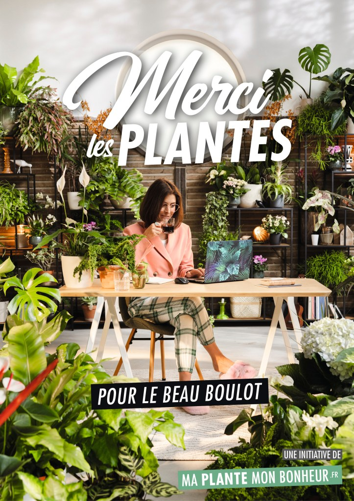 Femme derrière un bureau à la  maison entouré de plantes d'intérieur.