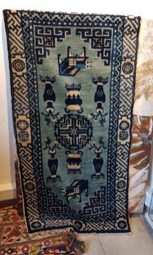 """Tapis """"Pao Tao"""" en laine ; à médaillon central décoré de vases et de meubles sur fond bleu, tissage traditionnel fait à la main avec jute (Fin 19ème siècle), CHINE - Dimension : 117 cm x 58 cm - Prix de vente : 690€."""