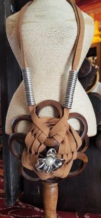 """Collier """"Fleur"""" en bois, lien en cuir serti d'éléments en métal argenté, INDONÉSIE - Prix de vente : 25€."""
