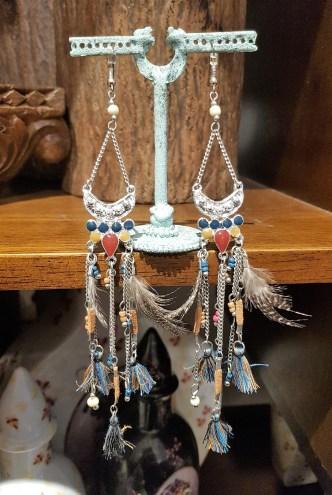 Boucles d'oreilles à trou en plume, plastron et chaîne en métal argenté, INDONÉSIE - Prix de vente : 40€.