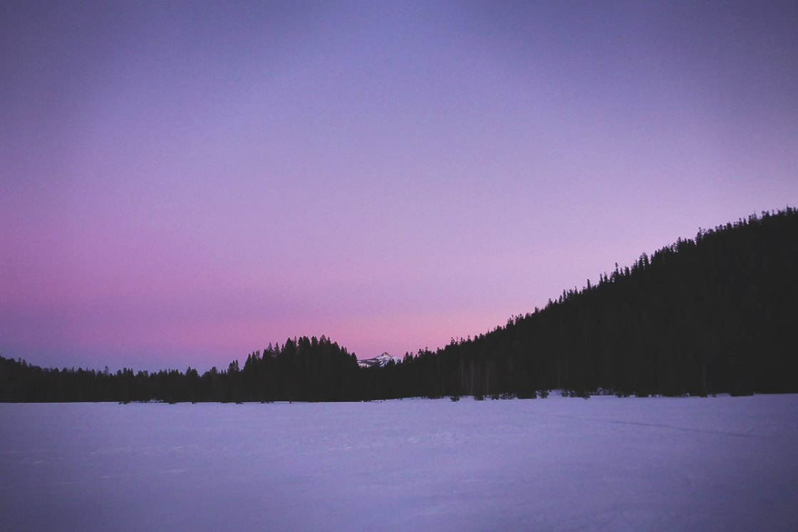Purple haze over the sky and snow on a mountain lake
