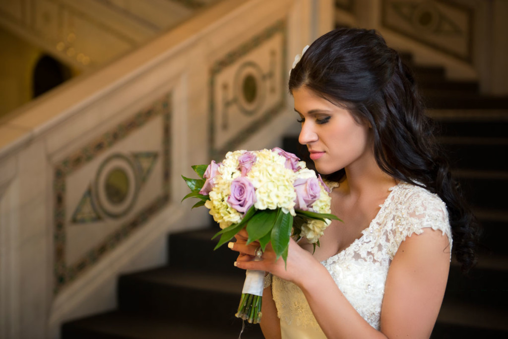 bride standin on the staircase in Chicago Cultural Center with flowers.