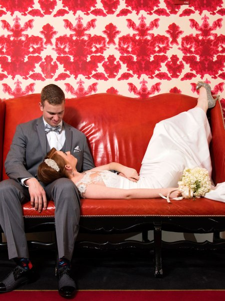 Bride and groom laying down on a red Couch in Blackstone Hotel