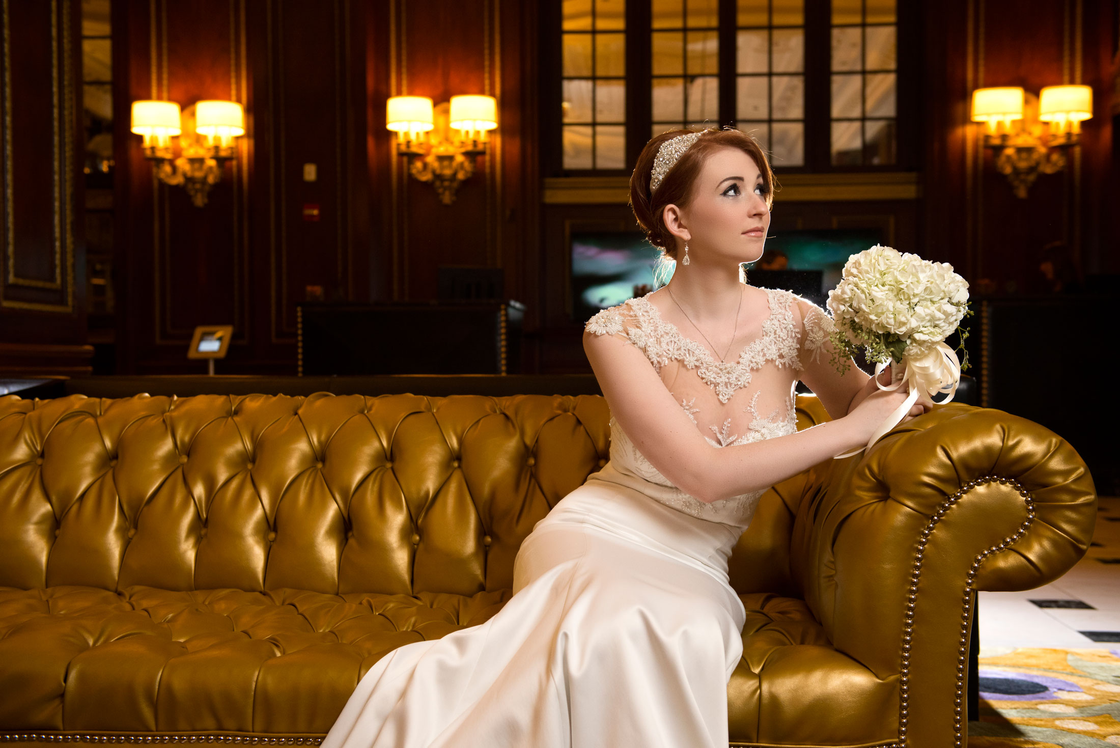Bride sitting on a golden couch in Blackstone Hotel in Chicago before her wedding