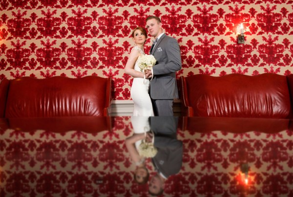 Bride and groom standing in front of famous red wall in blackstone hotel Chicago