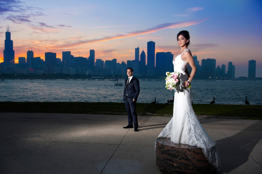Bride and groom standing before beautiful skyline sunset in Chicago