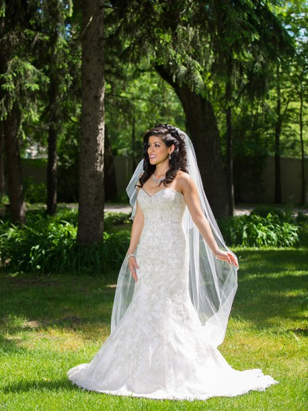 beautiful bride standing in a sunny field with trees in the background