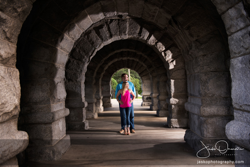 Engagement Session With Couple Standing Under Arches In Lincoln Park