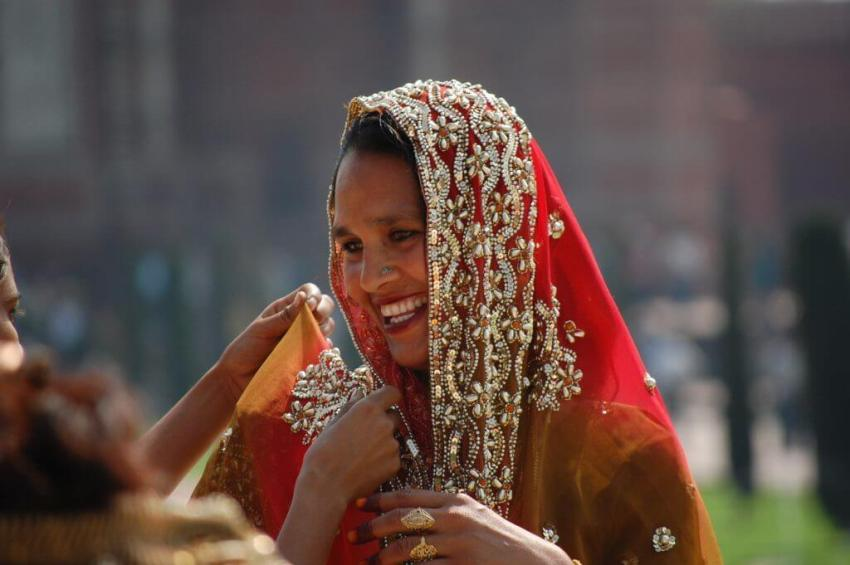 An Indian lady in bridal finery in front of Taj Mahal