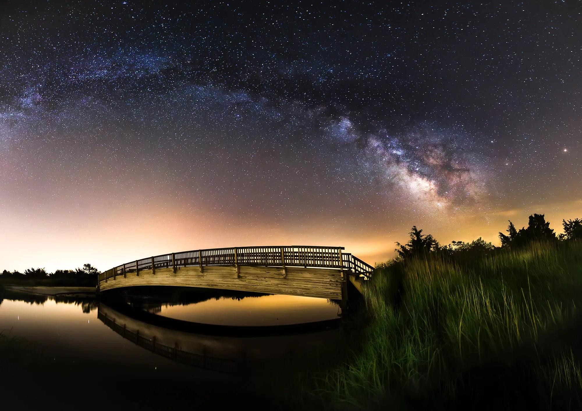 Milky Way spanning over a bridge