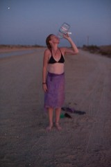 As the sun sets during an evening walk, Tammy finishes off her bottle of water. To stay hydrated in the desert heat, a person could drink an average of 3 to 4 liters of water each day. Slab City, California 2018