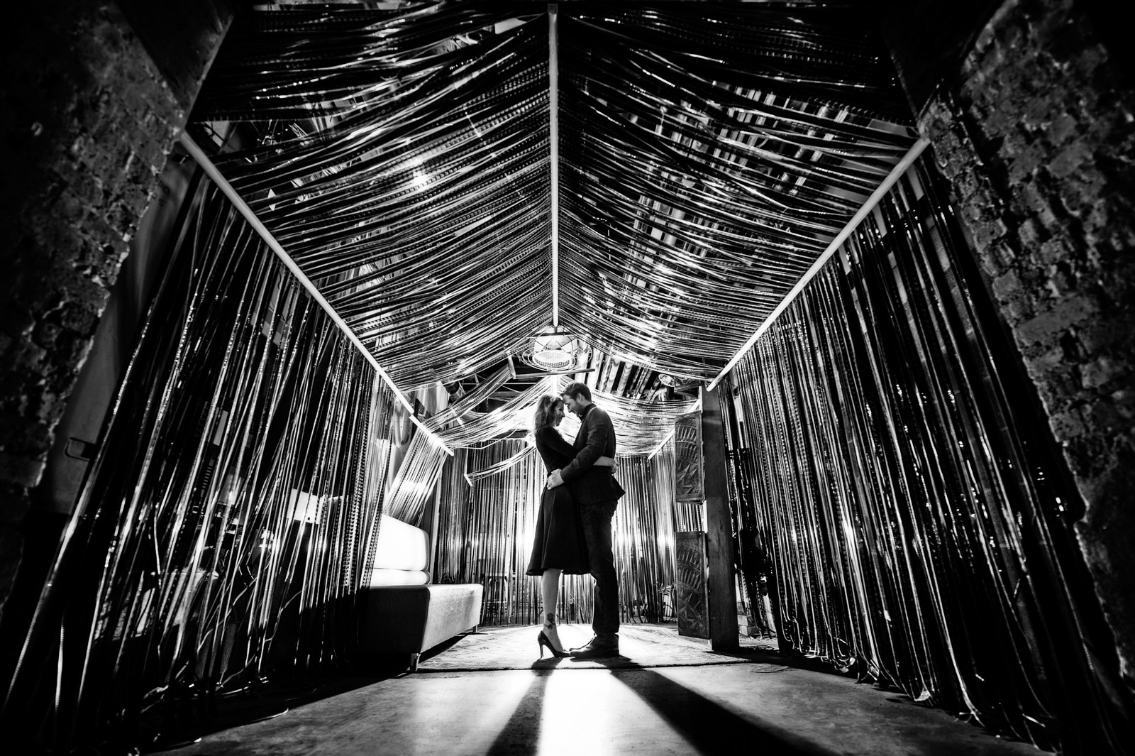Engagement Session photo in black and white of couple underneath film strips at Salvage One in Chicago