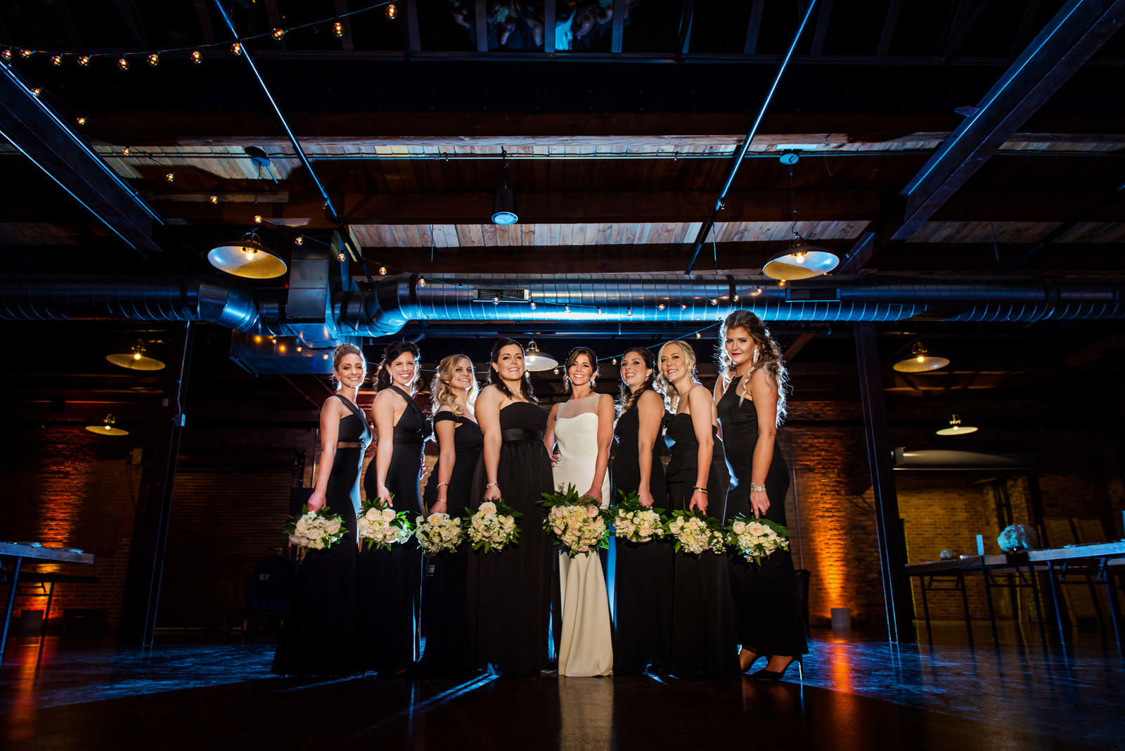 Bridesmaids in blue light holding wedding bouquets