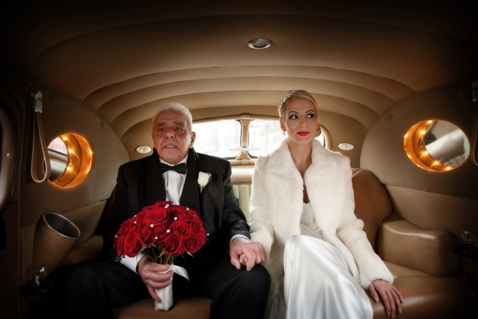 Father of the Bride and his daughter driving to wedding ceremony in classic car