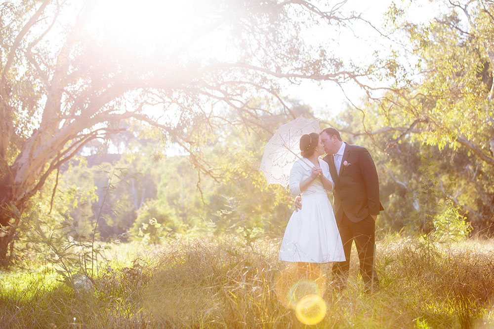 bride and groom in sunlight holding umbrella