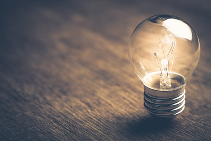 Small light bulb glowing on wood background