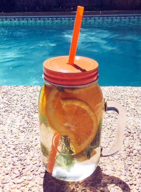 infused water in cup with oranges and basil
