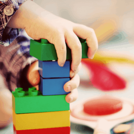 how to declutter toys child playing with blocks