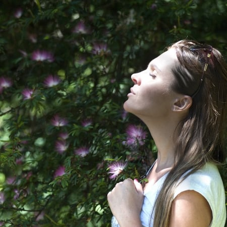 learn how to declutter your mind with woman surrounded by flowers taking deep breaths