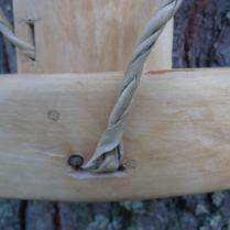 Närbild på hål för rem för att fästa allt vid trämesen