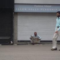 One man walking, the other sitting outside a closed shop