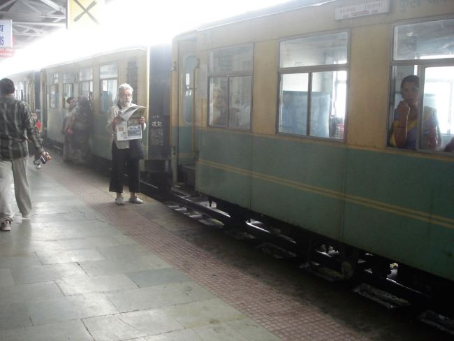Me standing att Shimla train station readin a newspaper