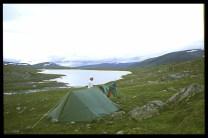 Tält i förgrunden, jag strå barkaom tältet. Bortom mig ligger en sjö, några fjäll i bakgrunden, Himlen är molning.