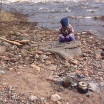 HannaBrita leker på en stor sten vid stranden. Framför henne är våran eld.