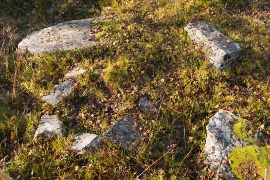 En gamal stensatt eldstad med en sten bredvid som man kan sitta på.