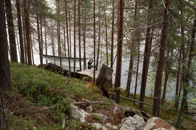 En tältplats i branten av ett berg, vid stranden av en sjö