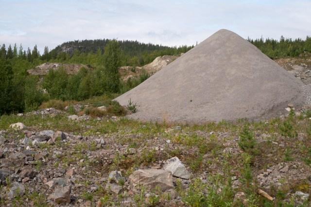 I förgrunden en sandhög, i bakgrunden ett berg