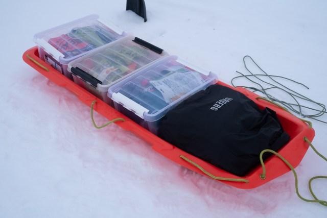 Pulka med packade plastlådor och en vattentät påse
