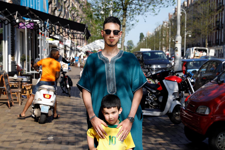 Jongeman met zonnebril en in blauwe kandora poseert met jongetje met voetbalshirt in de Javastraat