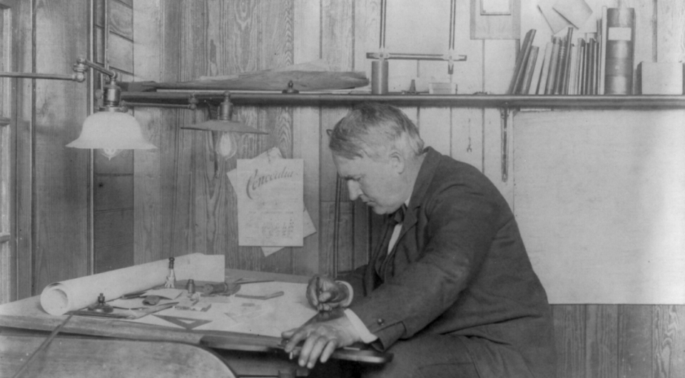 Thomas Edison writing at his desk, surrounded by the light bulbs he perfected, his journals, and his tools. Source: Wikimedia