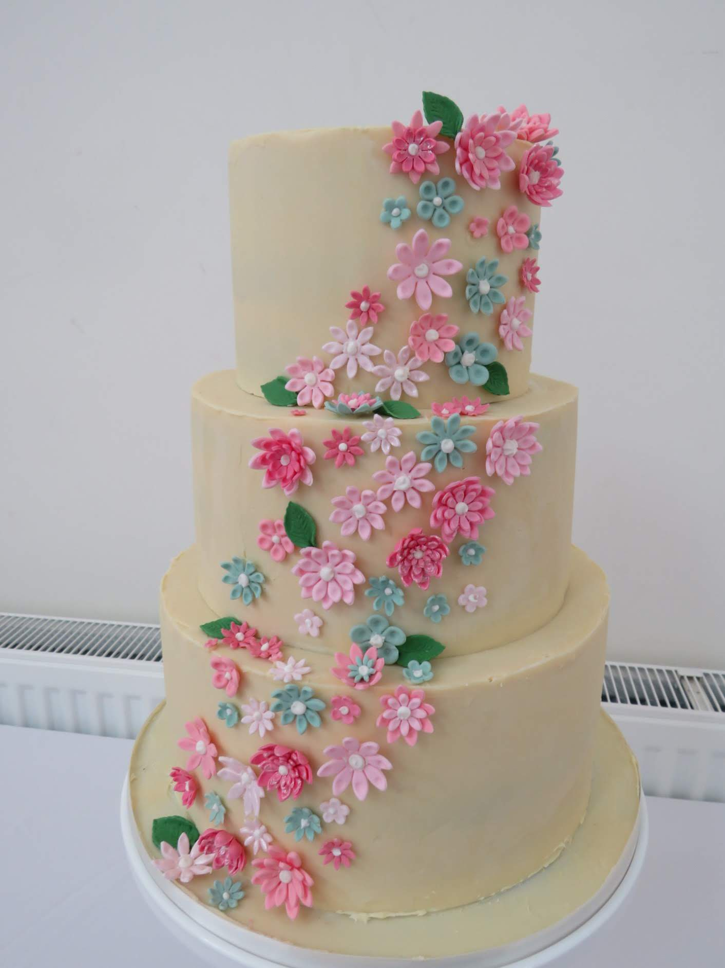 3 tier buttercream wedding cake with pink & green flowers down the front