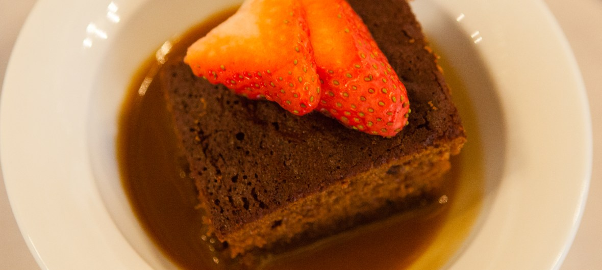 Sticky toffee pudding with fresh strawberry decoration